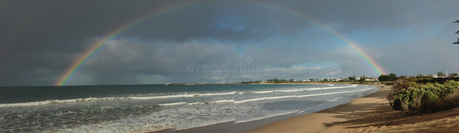 large complete full half circle rainbow stretching across the sky into the ocean at Apollo Bay, Victoria, Australia royalty free stock photography