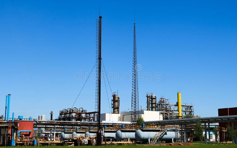 A large concrete technological industrial installation at a chemical petrochemical refinery with capacitive pipes by pumps. Compressors heat exchangers by stock image