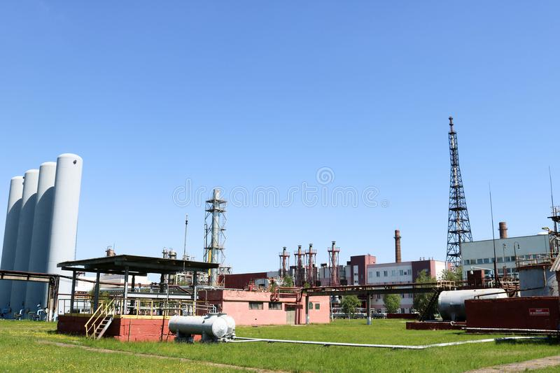 A large concrete technological industrial installation at a chemical petrochemical refinery with capacitive pipes by pumps. Compressors heat exchangers by royalty free stock images
