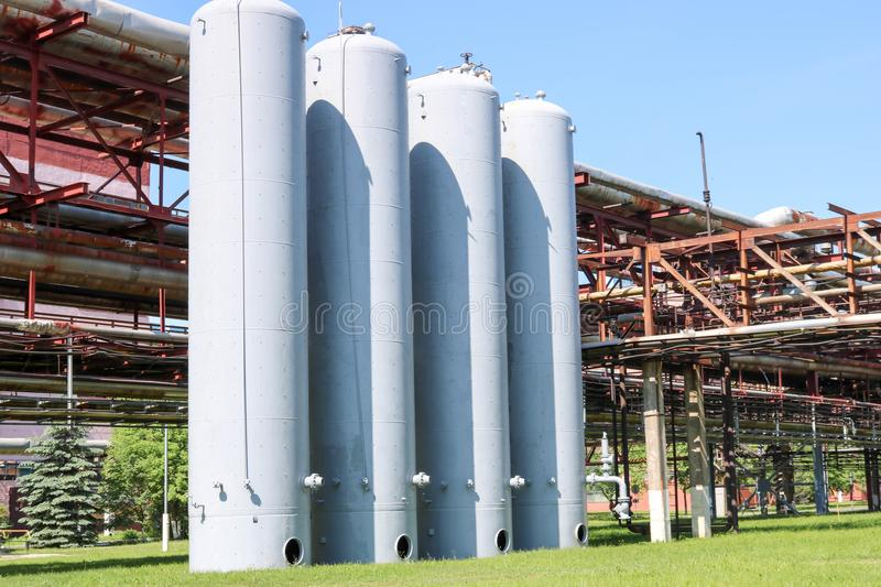 A large concrete technological industrial installation at a chemical petrochemical refinery with capacitive pipes by pumps. Compressors heat exchangers by royalty free stock photo