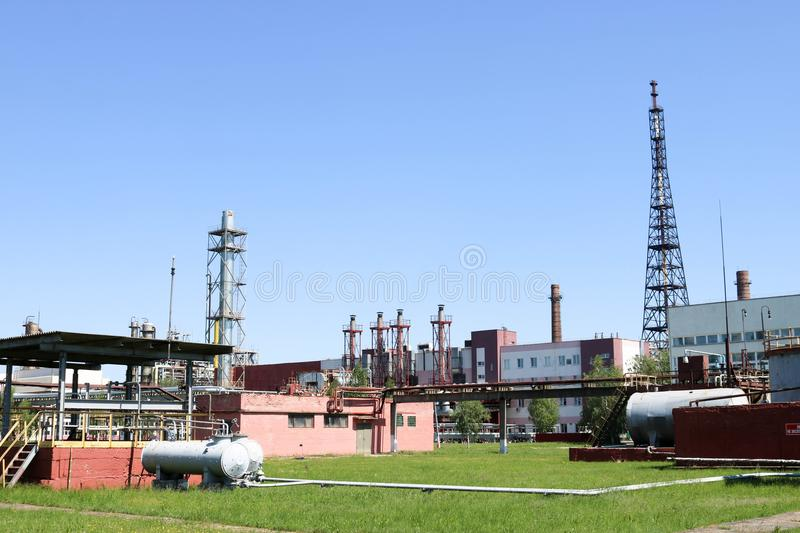 A large concrete technological industrial installation at a chemical petrochemical refinery with capacitive pipes by pumps. Compressors heat exchangers by royalty free stock photos