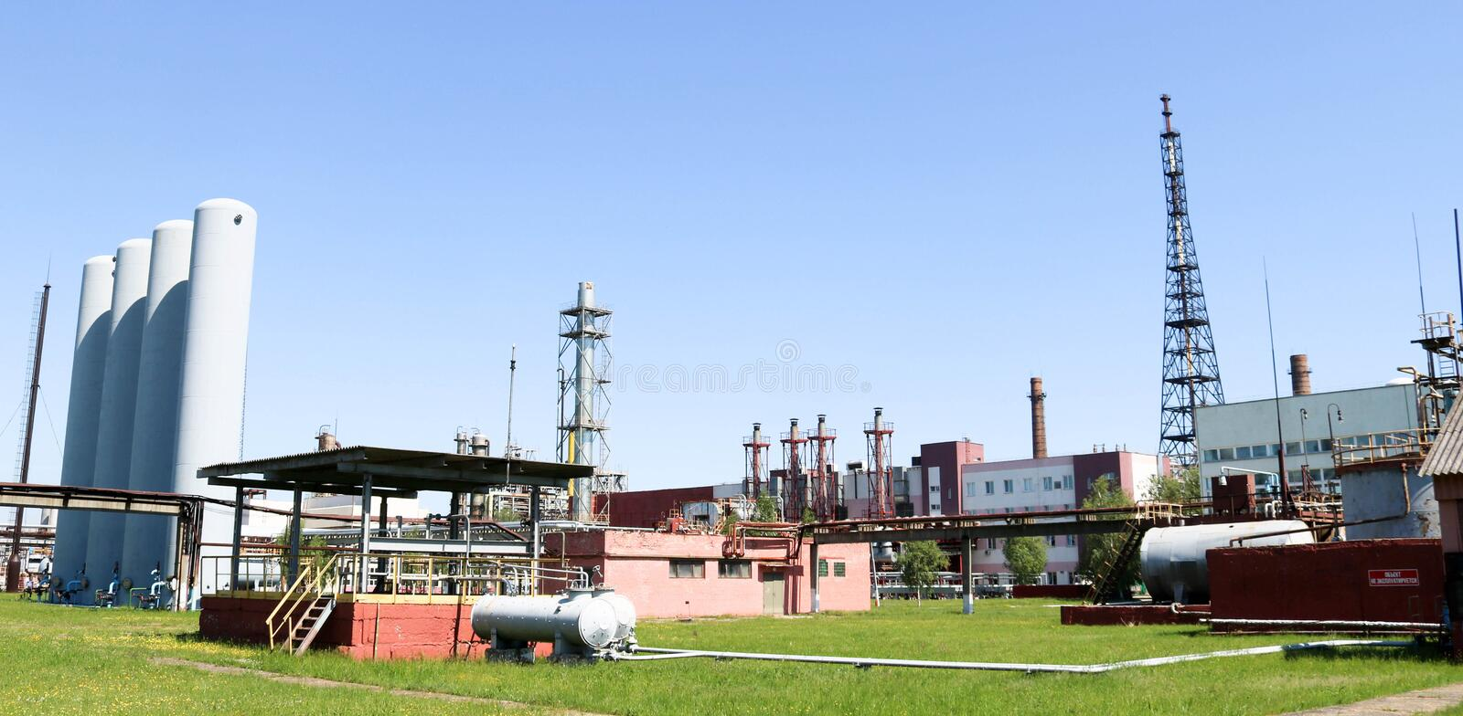 A large concrete technological industrial installation at a chemical petrochemical refinery with capacitive pipes by pumps. Compressors heat exchangers by royalty free stock photography