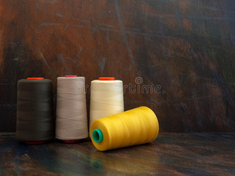 Industrial cones of sewing threads laying and standing on a dark background. Front view studio shot. stock image