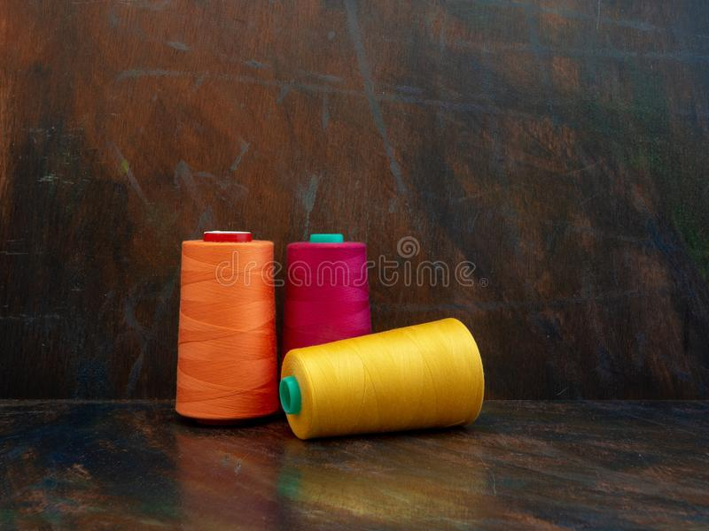 Industrial cones of orange, pink and yellow sewing threads laying and standing on a dark background. Front view studio shot. stock photography