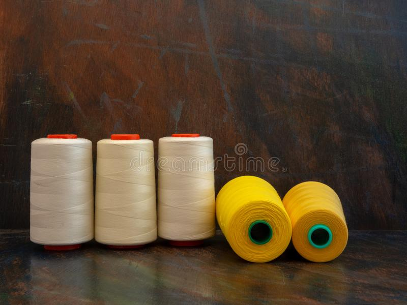 Industrial cones of yellow and white sewing threads laying and standing on a dark background. Front view studio shot. royalty free stock photography