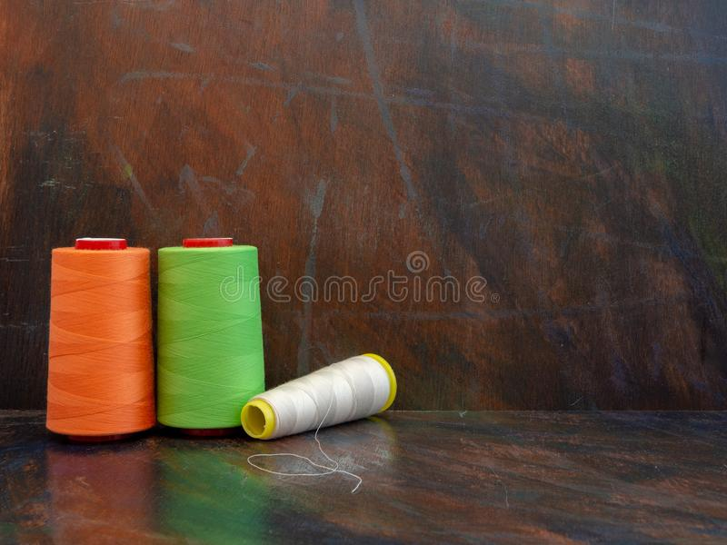 Large industrial cones of orange, green and white sewing threads laying and standing on a dark background. Front view studio shot. royalty free stock images