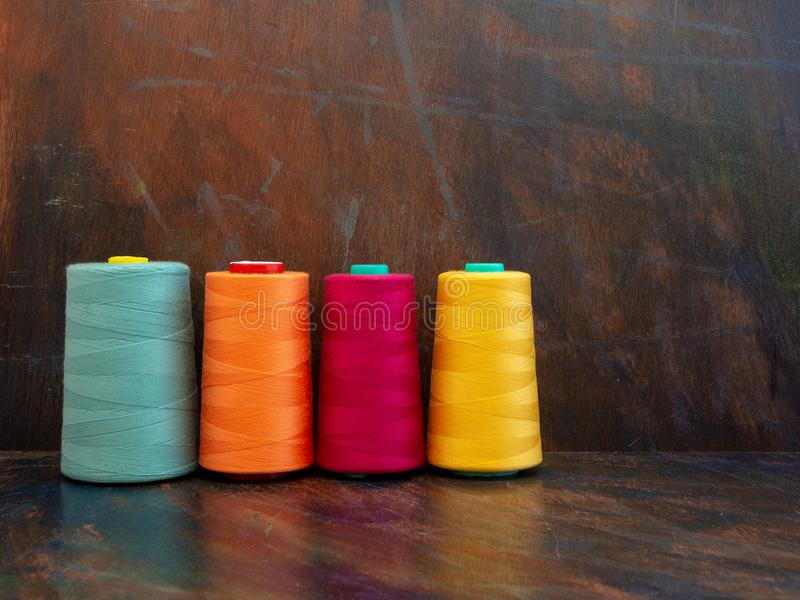 Large professional industrial cones of colorful sewing threads laying and standing on a dark background. Front view studio shot. royalty free stock photography