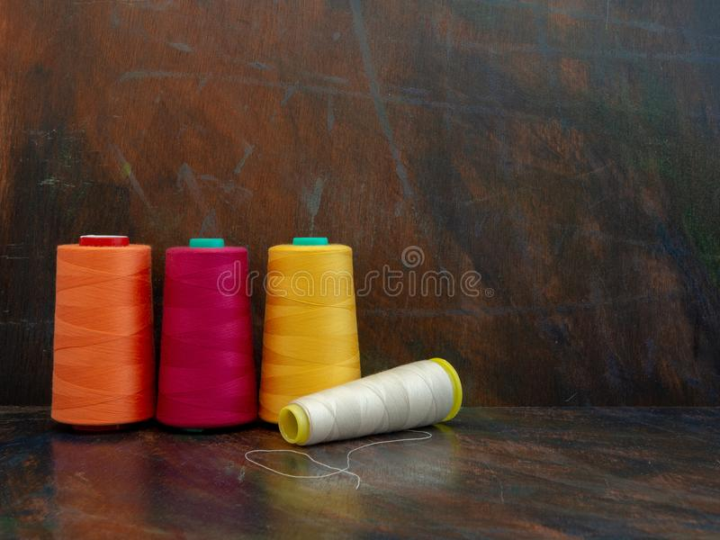 Professional industrial cones of colorful sewing threads laying and standing on a dark background. Front view studio shot. royalty free stock photo