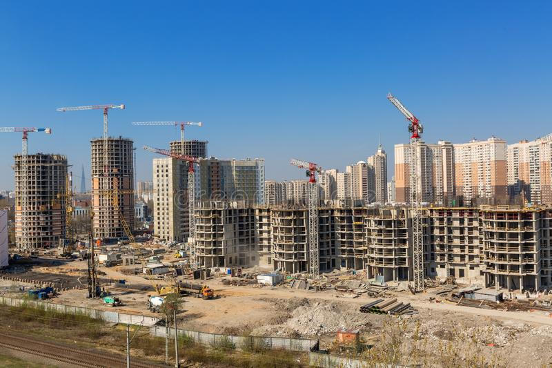 Large construction site including several cranes working on a building complex, workers, construction gear, tools and stock images