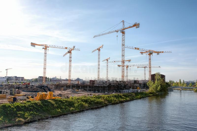 Large construction site with many cranes on a river, on a sunny, hazy day - Berlin 2018 stock photography