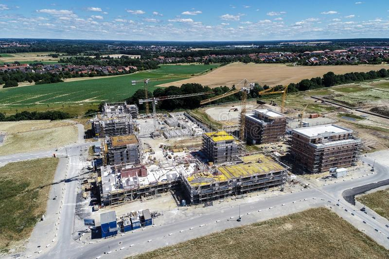 Large construction site on the outskirts behind a village with meadows and fields in front, aerial view royalty free stock photos
