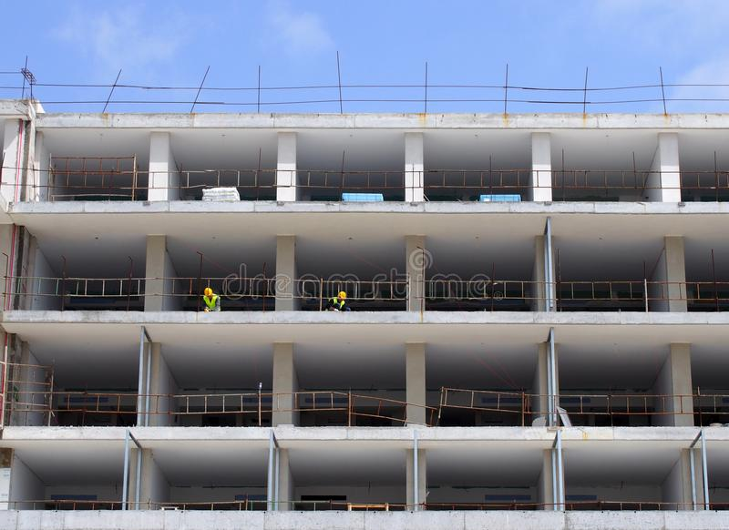 A large construction site of residential apartments with white concrete floors and workers in protective clothing with blue sky royalty free stock images