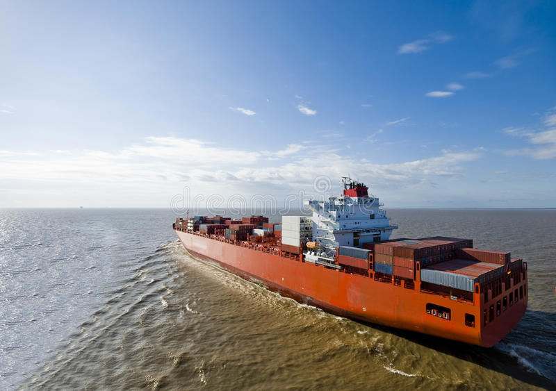 Large container vessel ship heading out to the sea. stock photography