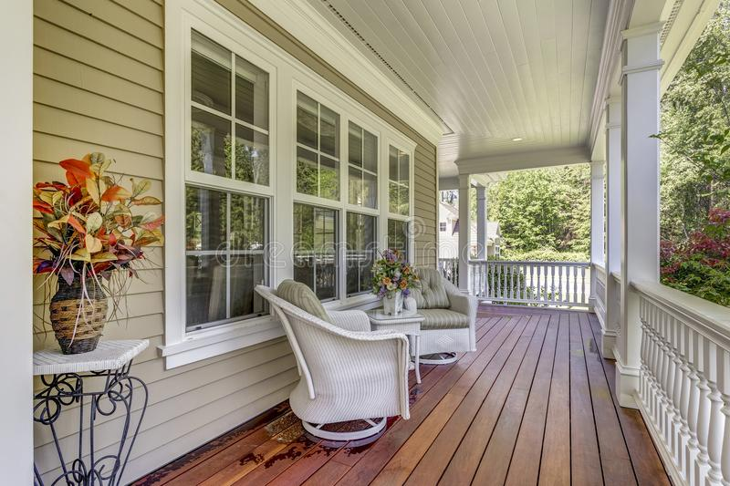 Large country home with wrap-around deck. Exterior view of a large country residence with wrap-around deck and cozy sitting area royalty free stock photography