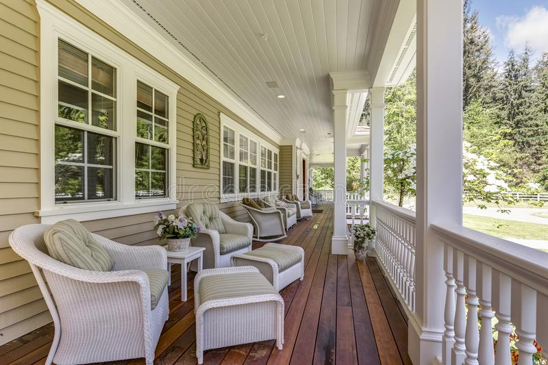 Large country home with wrap-around deck. Exterior view of a large country residence with wrap-around deck and cozy sitting area stock images