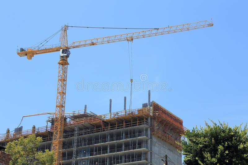 Large Crane at a Construction Site. Daytime image of a large crane over a high-rise construction site stock photo