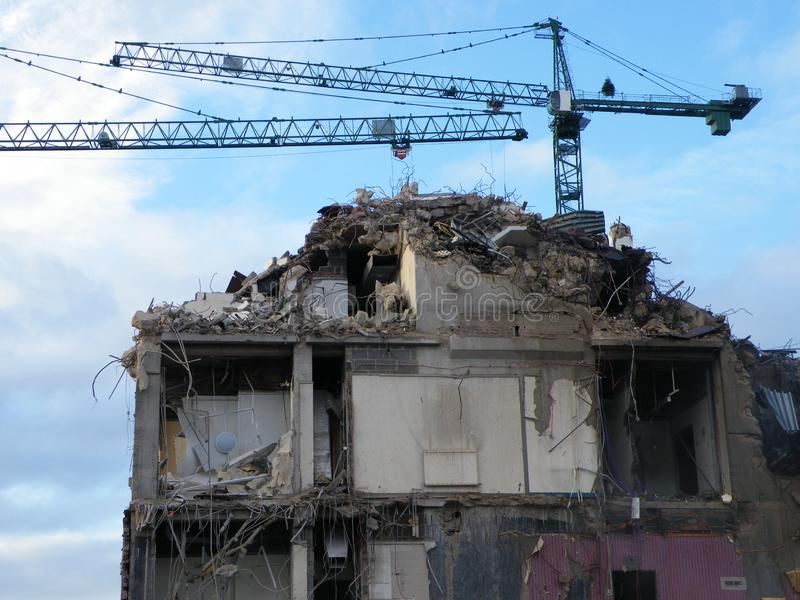 Large cranes over a large concrete building being demolished with exposed walls during redevelopment of a large urban site. Two large cranes over a large stock image