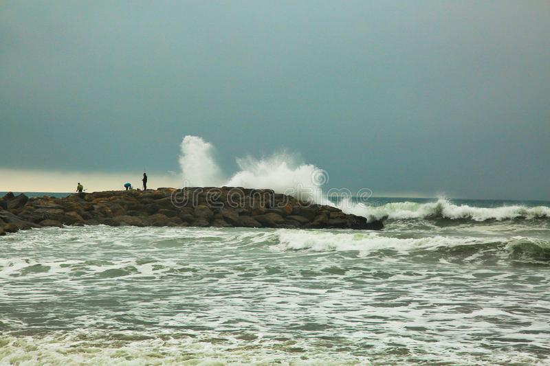 Fishing Oxnard California waves. Large crashing waves over rocks in Oxnard were people go stock photo