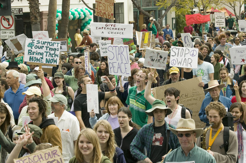A large crowd of protesters march and chant down State Street carrying signs at an anti-Iraq War protest march in Santa Barbara. California on March 17, 2007 royalty free stock image