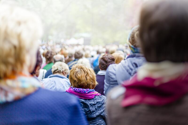 Large crowd of people in city park stock photos