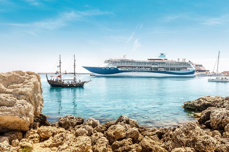 Large cruise ship and a small tourist pirate boat met in the resort port. A large cruise ship and a small tourist pirate boat met in the resort port royalty free stock photography