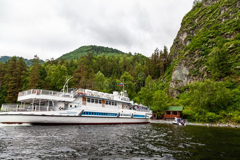 Cruise ship during a walk on the water on the Teletskoye lake in the Altai mountains with tourists near the pier with rocks. Large cruise ship during a walk on royalty free stock photography