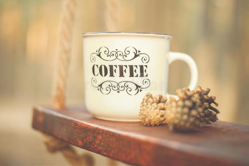 A large Cup labeled coffee stands on a wooden swing stock images