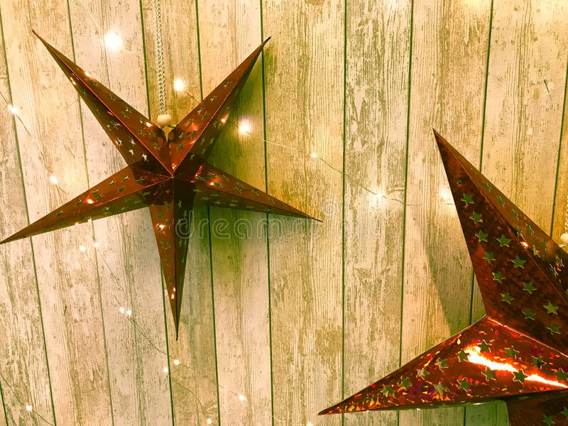 Large cute red holiday stars, Christmas, New Year`s decoration against the background of glowing gerlyand wooden vertical boards royalty free stock photo