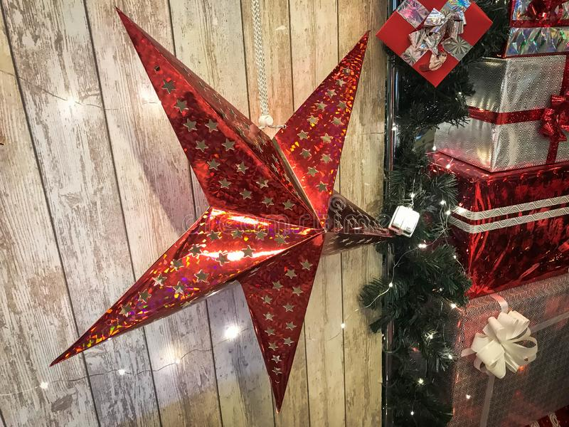 Large cute red holiday stars, Christmas, New Year`s decoration against the background of glowing gerlyand wooden vertical boards royalty free stock images
