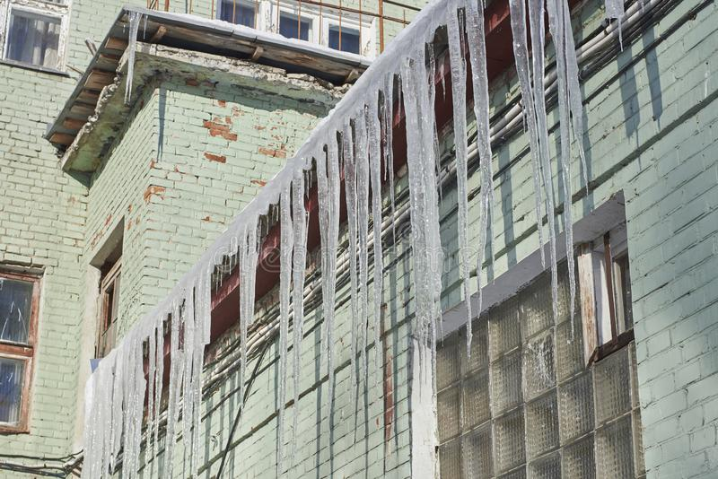 Large Icicles On The Roof Of The Building Stock Photo
