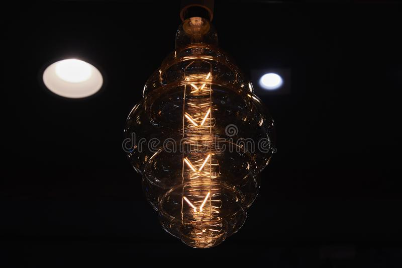 Large decorative incandescent lamp on a dark background. Numerous light sources are reflected in a glass bulb. Large decorative incandescent lamp on a dark royalty free stock photo