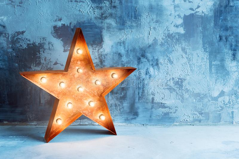 Large decorative retro star with lots of burning lights on grunge concrete background. Beautiful decor, modern design. Element. The loft style studio stock image
