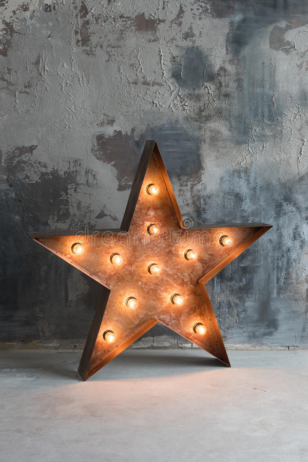 Large decorative retro star with lots of burning lights on grunge concrete background. Beautiful decor, modern design. Element. The loft style studio stock images