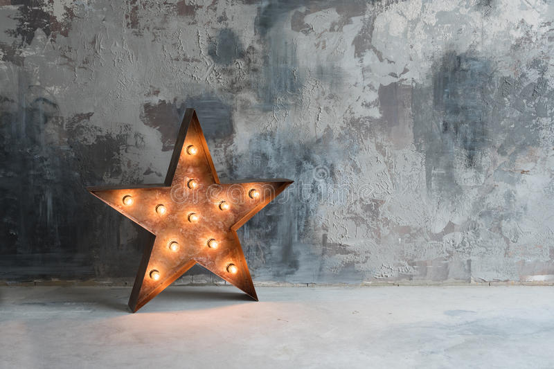 Large decorative retro star with lots of burning lights on grunge concrete background. Beautiful decor, modern design. Element. The loft style studio royalty free stock photos