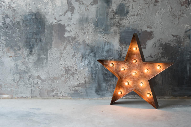 Large decorative retro star with lots of burning lights on grunge concrete background. Beautiful decor, modern design. Element. The loft style studio stock photo