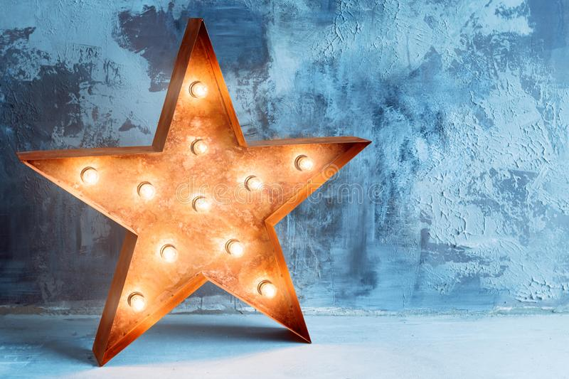 Large decorative retro star with lots of burning lights on grunge concrete background. Beautiful decor, modern design. Element. The loft style studio stock photos