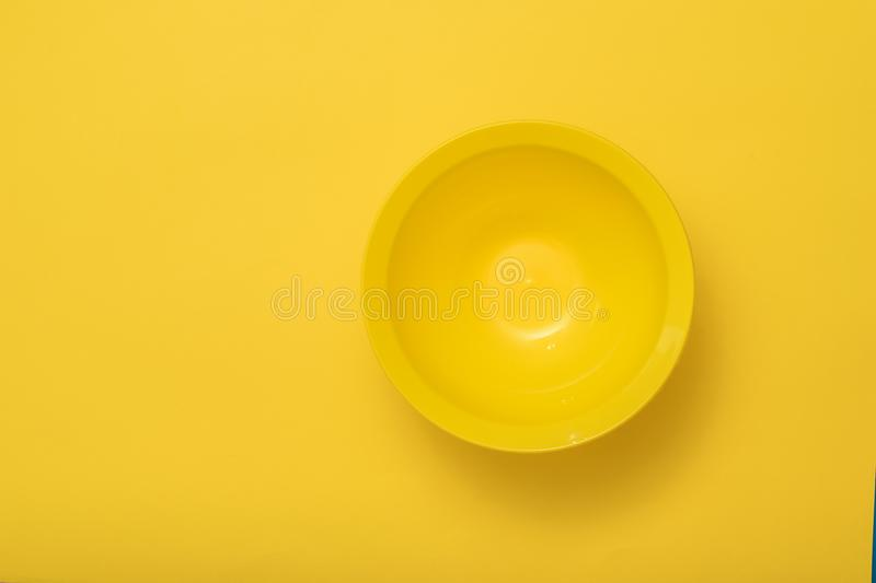 A large deep yellow bowl on a yellow background. royalty free stock photo