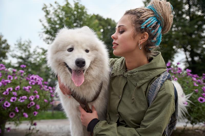 Large detailed horizontal portrait of a young stylish girl with dreadlocks and her white Samoyed dog. royalty free stock photography