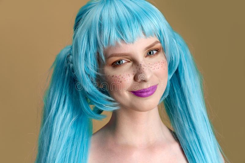 Large detailed Studio portrait of a young stylish woman with long blue hair and freckles with positive emotions on her face. And pure white skin. Bright stylish stock image