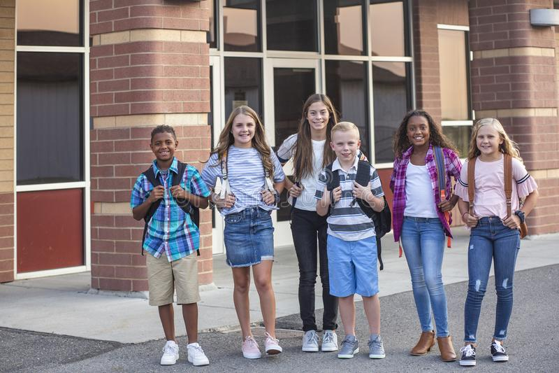 Large, diverse group of kids leaving school at the end of the day. School friends walking together and talking together on their w stock photography