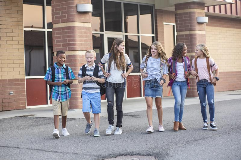 Large, diverse group of kids leaving school at the end of the day. School friends walking together and talking together on their w royalty free stock image