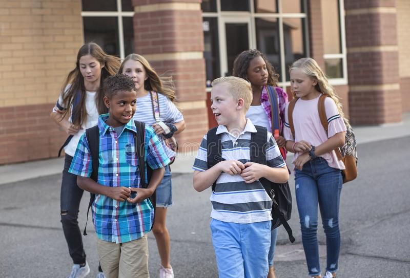 Large, diverse group of kids leaving school at the end of the day. School friends walking together and talking together on their w stock photo