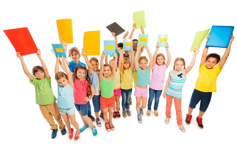 Large diverse group of kids lifting up textbooks stock photos