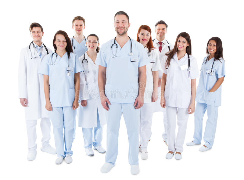 Large diverse group of medical staff in uniform. Large diverse group of medical staff in white uniforms standing grouped behind a handsome middle-aged bearded stock photo