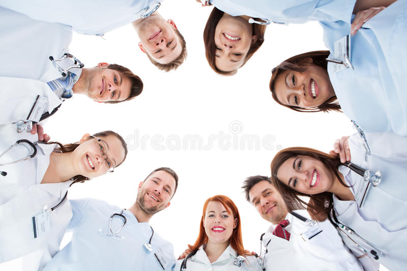 Large diverse multiethnic medical team. Standing grouped in a circle all looking down at the camera and smiling isolated on white with central copyspace