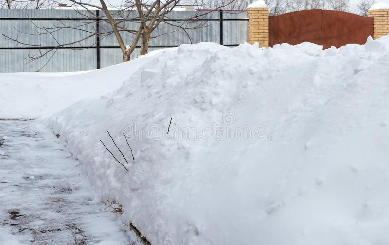 Large drifts of snow in the small yard. In a small courtyard cleared the path next to the large snowdrifts of white snow. Reference image stock photography