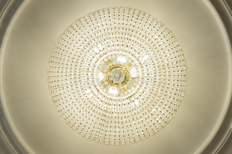 Large electric chandelier made of glass beads on a white decorative ceiling decorated with stucco molding stock image