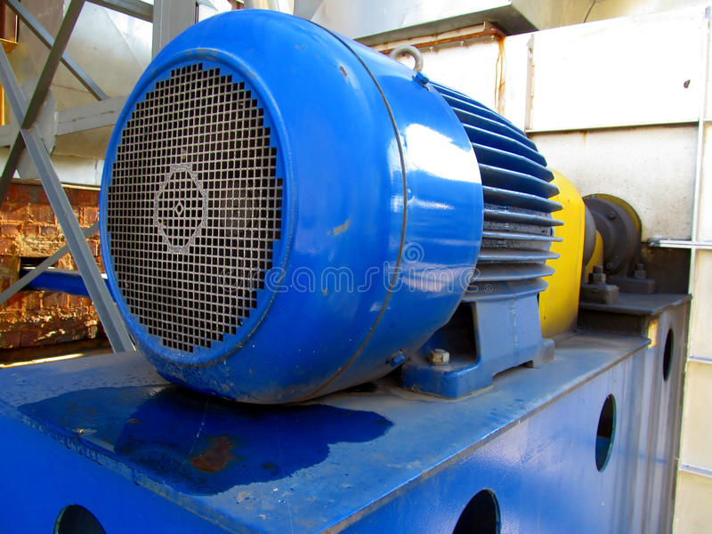 Large electric motor of blue color as the drive to the fan. Large electric motor of blue color as the drive to the exhaust fan stock photography