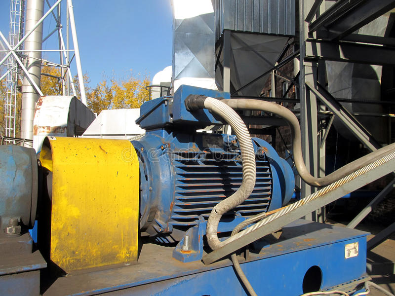Large electric motor of blue color as the drive to the fan. Large electric motor of blue color as the drive to the exhaust fan stock photos