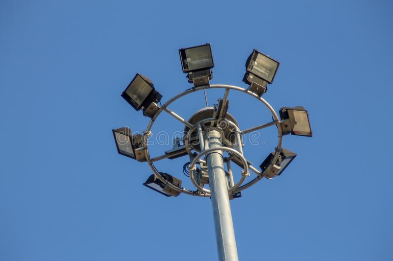 A large electric pole filled with spotlights in the blue sky royalty free stock photos